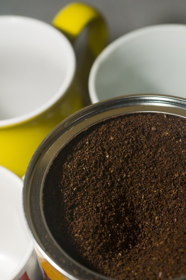 can of ground coffee beans with mugs