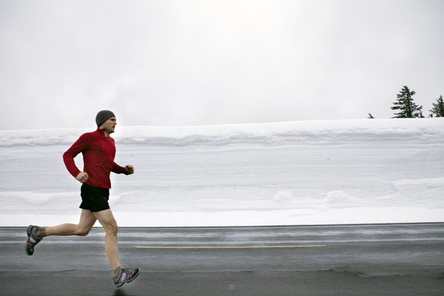 Man jogging down road with heavy snow.