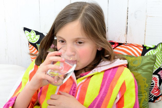 sick girl drinking a glass of water