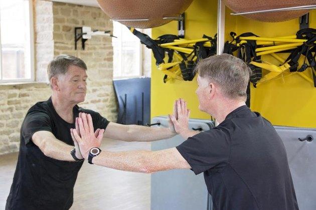 Senior man doing press ups on gym mirror.