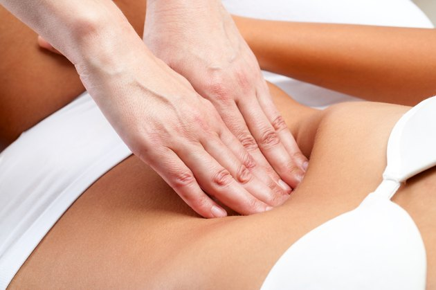 Therapist Hands pressing on female abdomen.