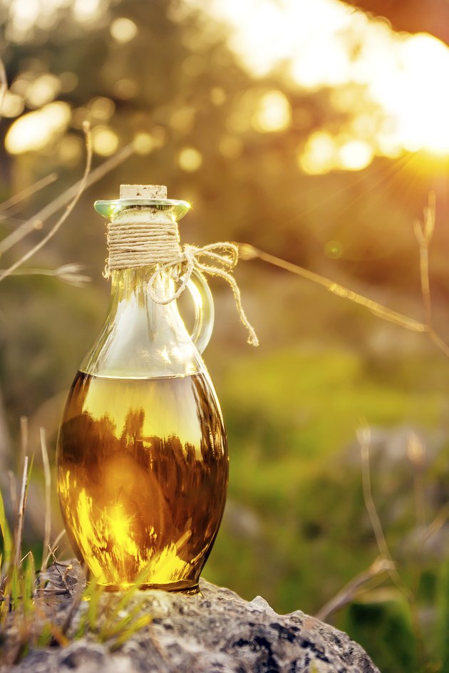 Little bottle with olive oil with lens flare and sun light