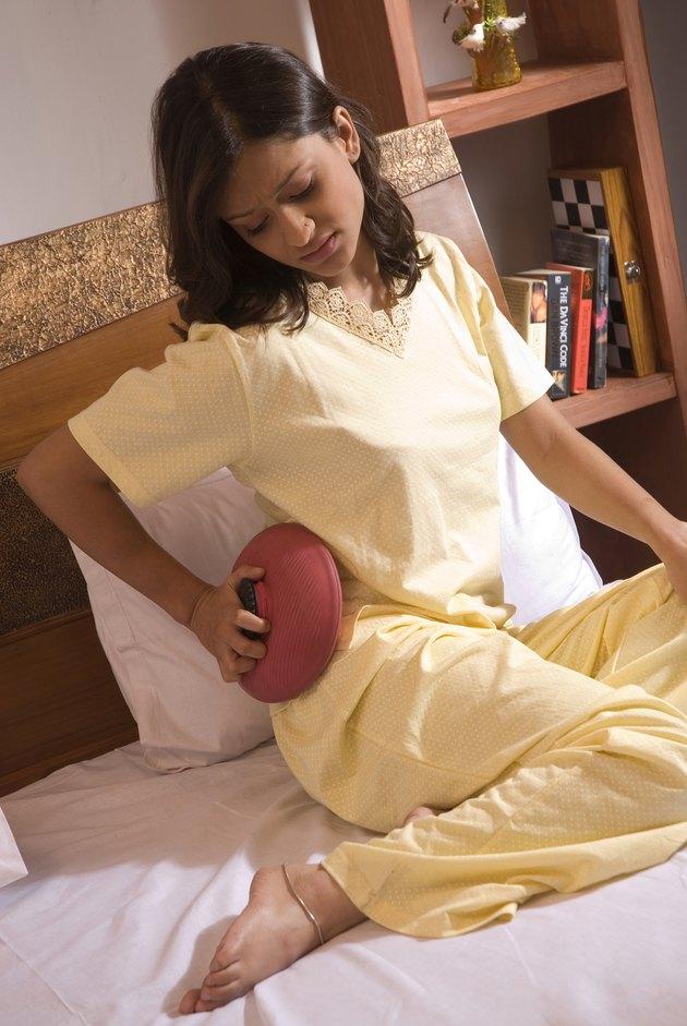 A woman applying a hot water bag