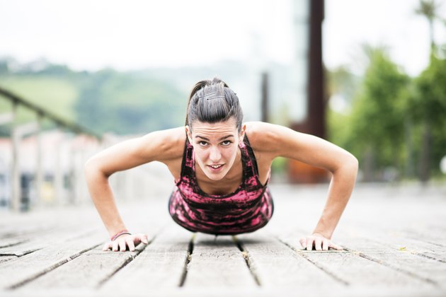 Young Woman Exercising Push-Ups on Wooden Floor.