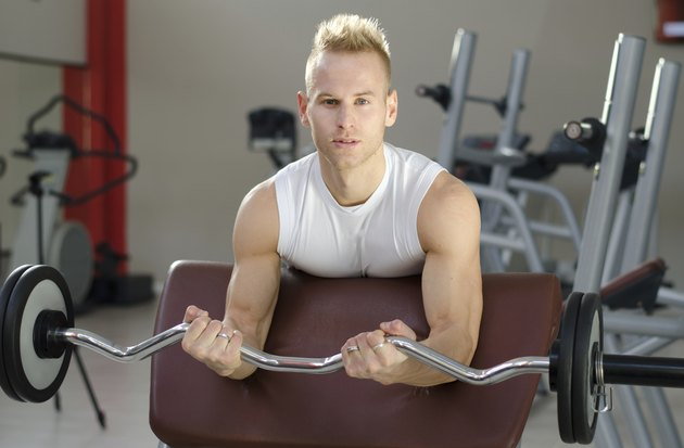 Handsome young man training biceps in gym