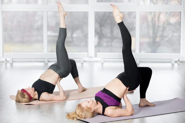 Fitness, stretching practice, group of two attractive fit mature women working out in sports club, 'warming up', doing backbend pose, one-legged shoulder bridge exercise in class, full length