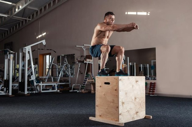 Man box jumping at a gym style gym.