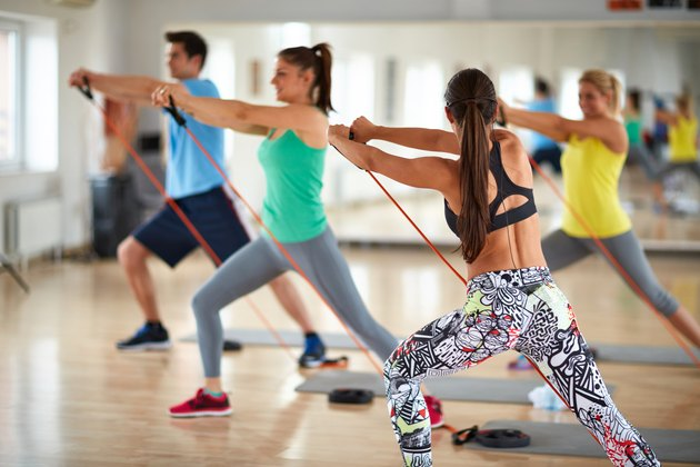 Woman with group of exercisers expands resistant rubber