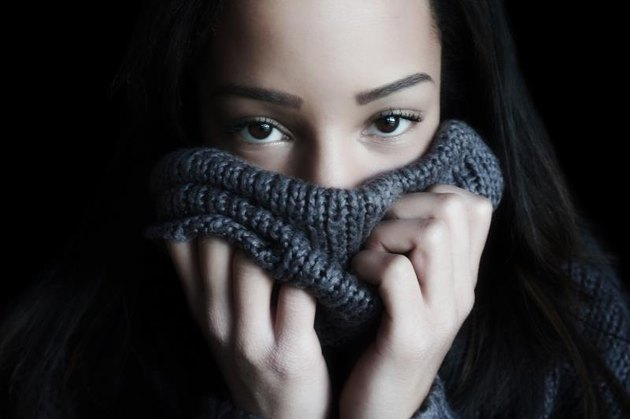 A young woman covers her face with a turtleneck, so that only the eyes and forehead are visible.