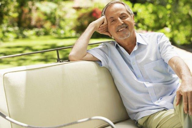 Senior Man Sitting On Sofa In Backyard