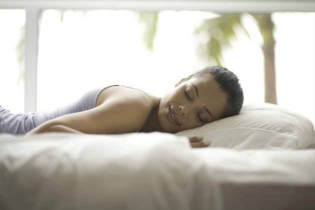 Side profile of a young woman sleeping on a bed