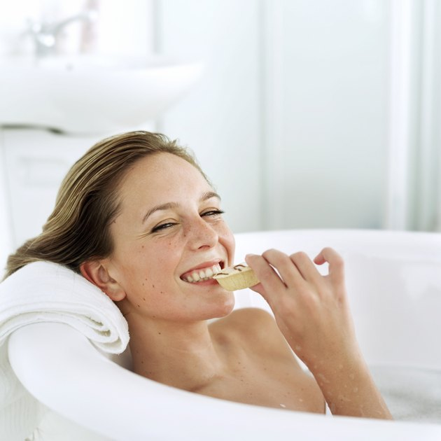 portrait of a young woman in a bathtub eating a snacking and smiling