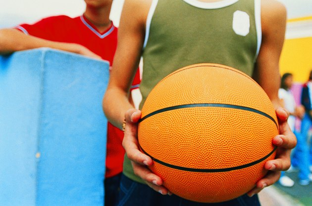 close-up of a teenage boy's hands holding a basketball