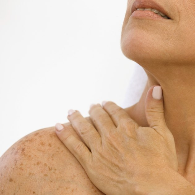 Woman rubbing her shoulder, close-up
