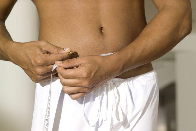 Man measuring around his waist, close-up, part of