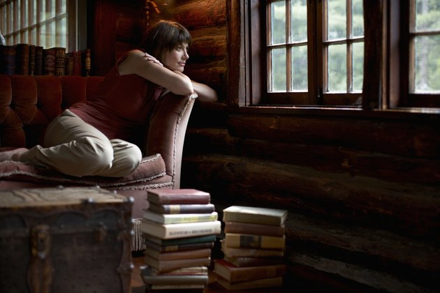 Woman sitting on sofa by stacks of books, looking out window