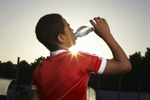 Boy (12-13) drinking water, rear view