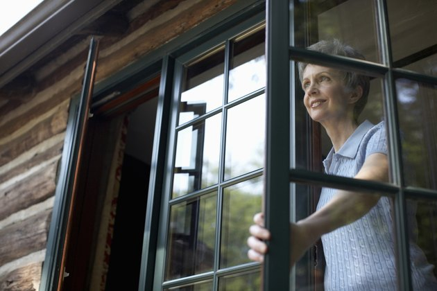 Senior woman looking through open window