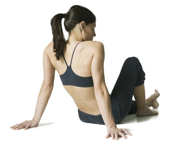 full body shot of a young adult woman in a black workout outfit as she sits and relaxes