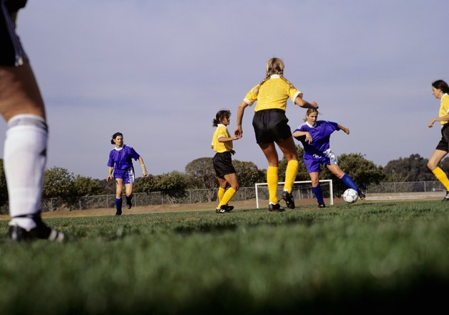 Young women playing football on grass pitch, surface view