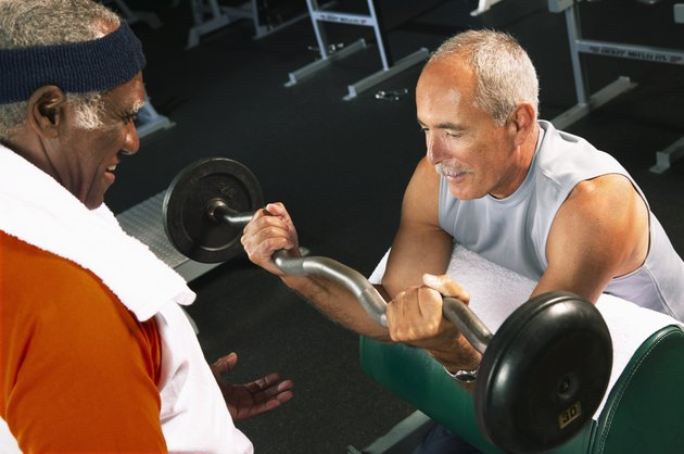 Senior man helping mature man weight train in gym