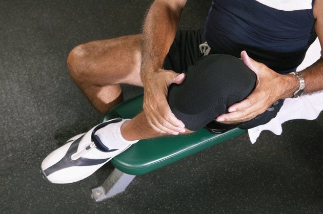 Senior man in gym wearing knee strap, lifting knee, overhead view
