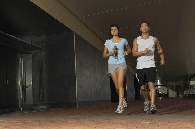 Young couple jogging in building complex