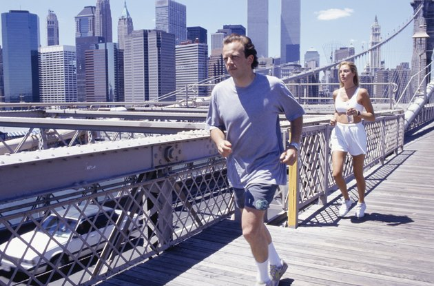 USA, New York City, man and woman jogging on Brooklyn Bridge