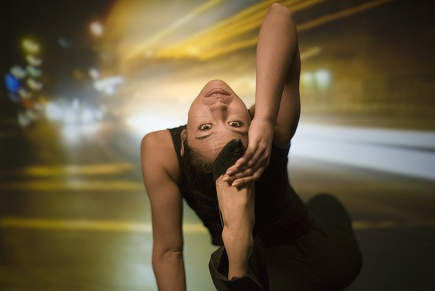 Young woman stretching, street scene projected in background