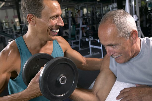 Two mature men in gym, one lifting weights