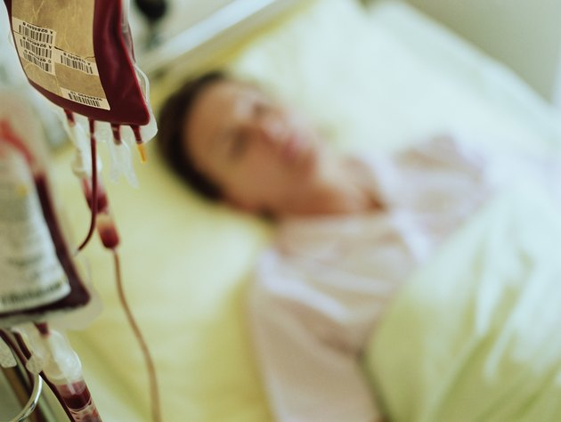 Woman in hospital bed by IV drip filled with blood (focus on drip)