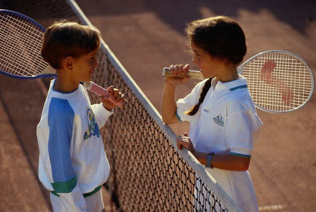 Children (6-9) face to face on tennis court