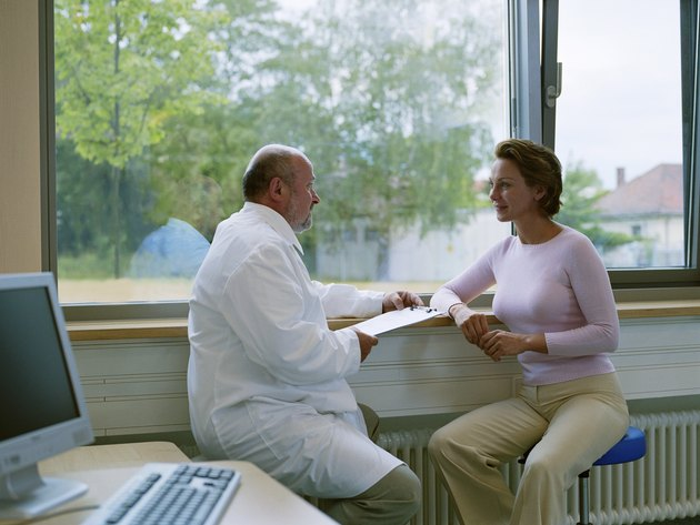Male doctor sitting with female patient by window, smiling