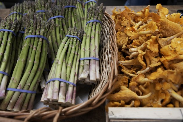 Basket of asparagus and chanterelle mushrooms on market stall