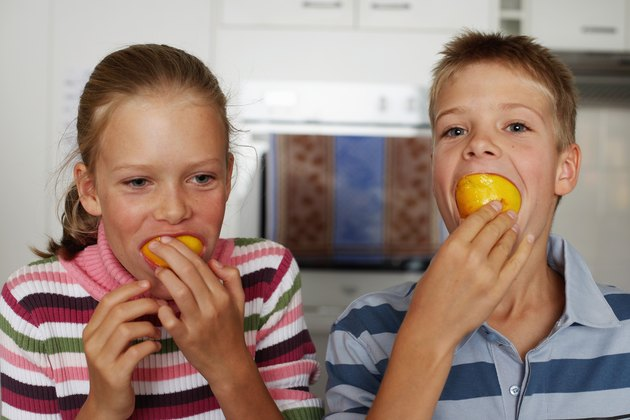 Twin brother and sister (10-12) with oranges in mouths, close-up