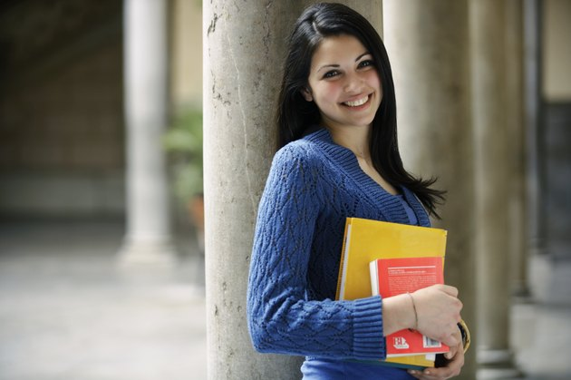 Young woman leaning against column holding books, smiling, portrait