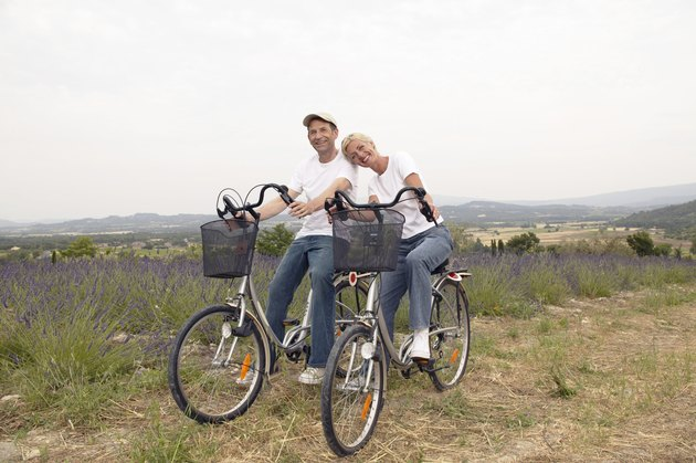 Mature Couple Sit Side by Side on Bicycles in a Lavender Field, Provence, France