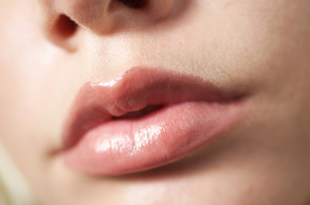 an extreme closeup of a young caucasian girl pursing her lips