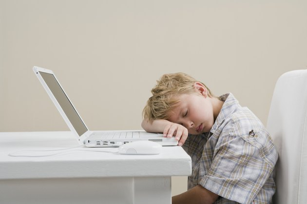 Boy (10-11) sleeping by laptop at table