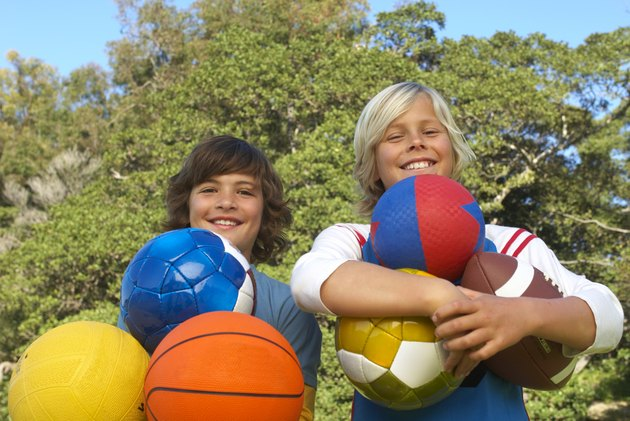 Two boys (11-13) holding sport balls outdoors, smiling, portrait, low angle view