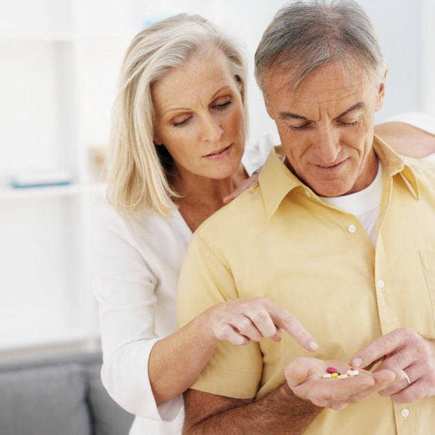 Close-up of mature man holding pills and mature woman looking at pills