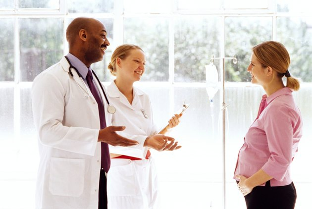 portrait of a young doctor and nurse talking to a pregnant woman