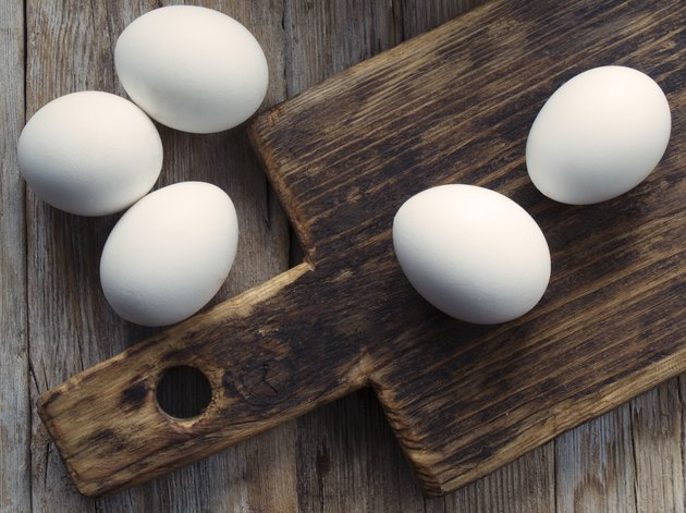 White eggs and a cutting board on a wooden table.