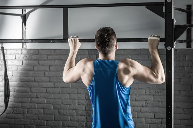 Active man makes a pull-up on the crossbar in the gym on the gray brick wall background. He wears a blue sleeveless. Shoot from the back. Horizontal.