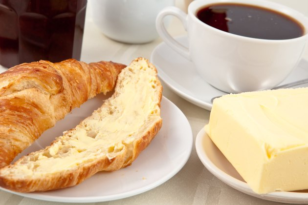 Breakfast with a croissant spread with butter