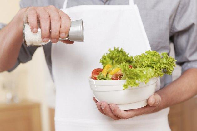 Salting salad.