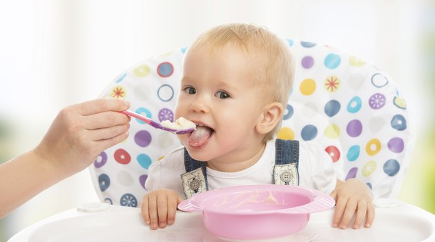 happy mother feeds funny  baby from  spoon