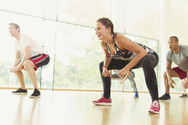 Smiling woman squatting in aerobics class