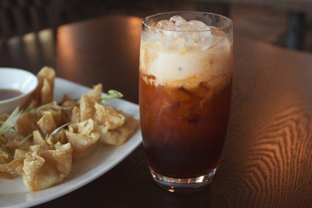 Thai iced tea on table with fried wontons