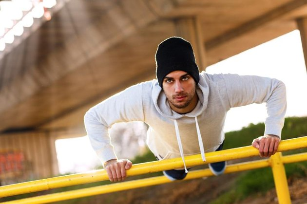 Young man doing push ups on the handrail under the bridge.